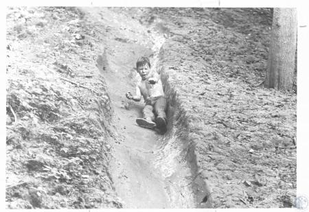 Image: di23236 - Joey Young (11) going down mud slide at Camp Bethel